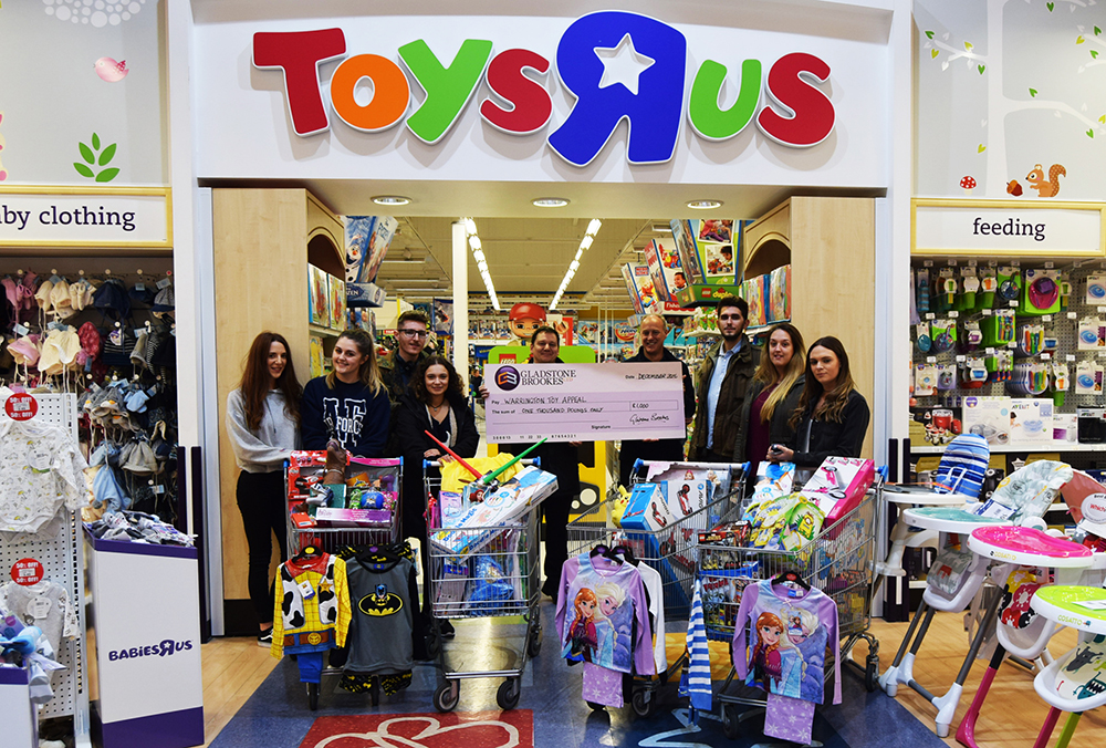 Our eight volunteers pictured with appeal organiser Paul Whittaker (centre back row) after their £1,100 trolley dash around Toys 'R' Us
